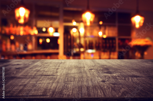 Image of wooden table in front of abstract blurred restaurant lights background - 259987581