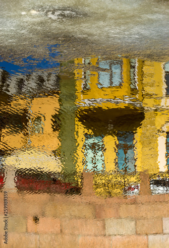 Reflection of houses on the waterfront in the water of the river - 259989359