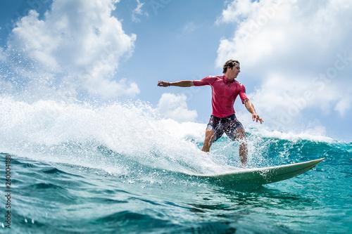 Leinwandbild Motiv Surfer rides the wave at sunny day