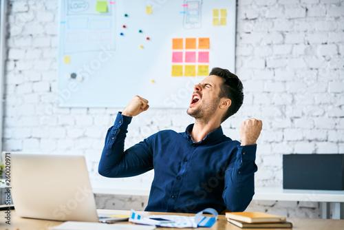 Leinwandbild Motiv Ecstatic web developer screaming in joy and making gestures celebrating success while sitting in office