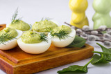 Deviled eggs with avocado and spinach on festive Easter table