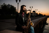 the saxophanist plays in the evening outside