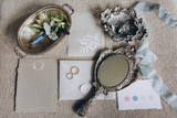 Wedding rings, vintage mirror, groom's boutonniere, invitation cards and an envelope are lying on the table
