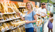 Woman choosing bread in bakery section