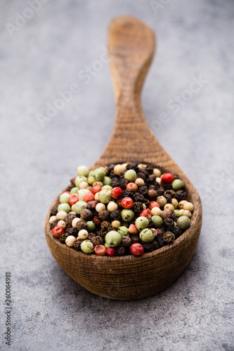 Peppercorn mix in a wooden bowl on grey table. © gitusik