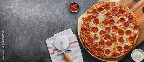 pepperoni pizza on wooden serving board shot top down with copy space composition - 260072146