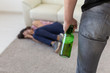 Victim, domestic violence, abuse and alcoholic concept - drunk man with bottle near his wife lying on the floor