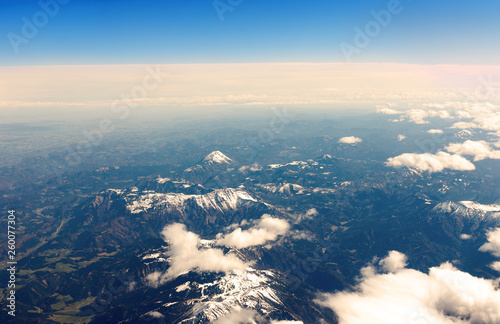 beautiful clouds from above with sow covered mountains - 260077304