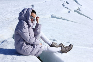 Girl in warm down-padded coat enjoys a look at snow top. Winter fashionable shot.