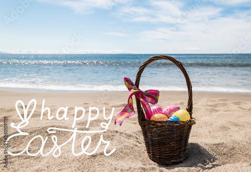 Leinwandbild Motiv Easter bunny with color eggs on the ocean beach