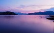 Beautiful violet sunset with reflexions in the motionless ocean - Island and hills in the background - panoramic