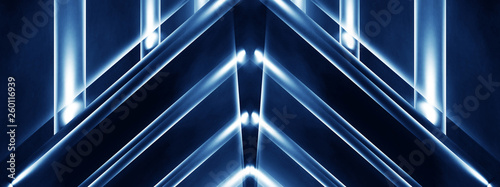 Abstract blue background with lines and rays of neon light. Reflection in space of symmetry. Abstract tunnel in motion. - 260116939
