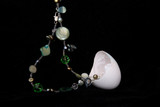 From the egg shell the necklace will rise with precious stones. Black background.