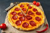 Smakowita pepperoni pizza pomidory i składniki na betonowym tle.