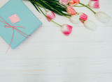 A bouquet of beautiful tulips and a gift on a wooden background top view
