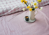 Morning breakfast in bed wooden tray with a cup of coffee and bouquet of flowers daffodils.