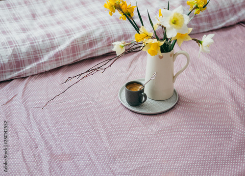 canvas print picture Morning breakfast in bed wooden tray with a cup of coffee and bouquet of flowers daffodils.