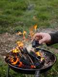 Hand puts coals into a burning fire in a compact grill, nature