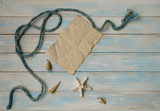 Seashells, nautical knot and star on blue wooden background and sheet of paper as a vacation concept with copy space - 260150183