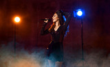Beautiful singing girl curly afro hair singer sing with microphone karaoke song on stage on dark neon light