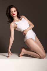 Sporty slim woman in white body. Gray background.