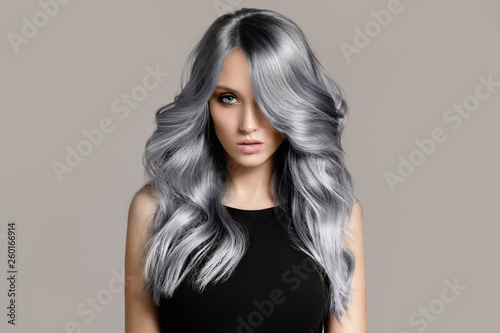 Leinwandbild Motiv Beautiful woman with long wavy coloring hair. Flat gray background.