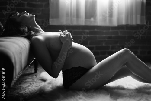 canvas print picture Sexy pregnant young woman holding breasts sitting on rug
