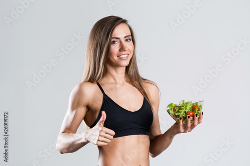 Fototapeten Fitness Fit woman with a salad isolated.