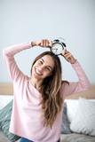 Joyful woman with alarm clock at home.