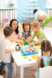 Leinwanddruck Bild - Educator helping kids playing with block constructor in daycare