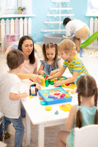 Leinwanddruck Bild Educator helping kids playing with block constructor in daycare
