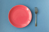 pink empty plate with fork and knife