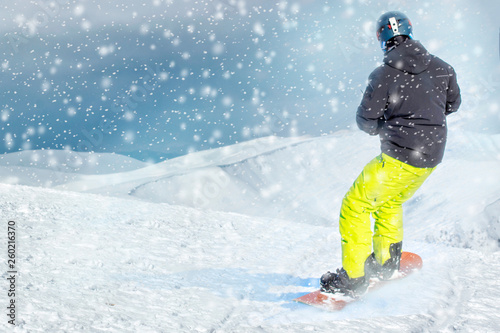 fototapeta na ścianę Freeride snowboarder rolls on a snow-covered slope leaving behind a snow powder. space for text
