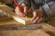 measuring with a centimeter and a pencil by a carpenter in a woodworking workshop - 260224724