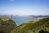 Golden Gate Bridge shot from a high point. Strait of the Golden Gate. Sunny weather and green vegetation.