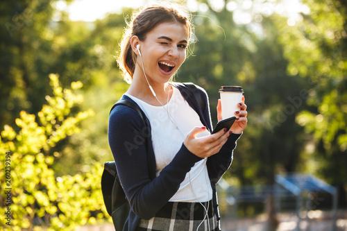Smiling young teenage girl carrying backpack walking