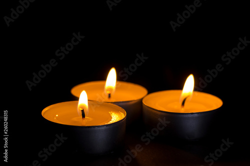 three small candles lit in the dark closeup © Nikolay