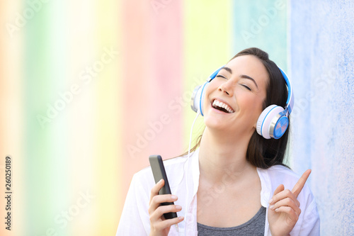 Happy girl singing listening to music in a colorful street - 260250189