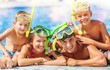 Leinwanddruck Bild - Happy family playing in swimming pool. Summer vacation concept
