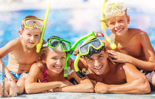 Leinwanddruck Bild Happy family playing in swimming pool. Summer vacation concept