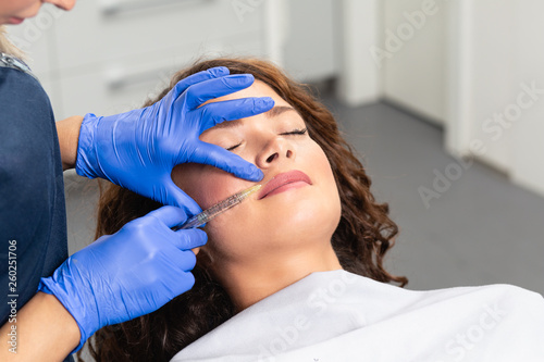Leinwandbild Motiv Attractive young woman is getting a rejuvenating facial injections. She is sitting calmly at clinic. The expert beautician is filling female wrinkles by hyaluronic acid.