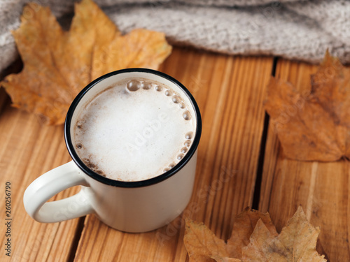 fototapeta na ścianę Autumn cappuccino with cinnamon on wooden background. Hot coffee with dry leaves and scarf