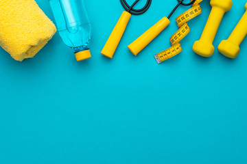 flat lay photo of yellow fitness equipment in oder over turquoise blue backgound