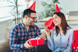 Beautiful young couple is celebrating at home. Handsome man is giving his girlfriend a gift box