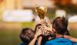 Leinwandbild Motiv Children Celebrating Sport Success Outdoor. Boys Holding Golden Cup