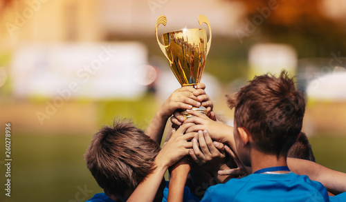 Children Celebrating Sport Success Outdoor. Boys Holding Golden Cup
