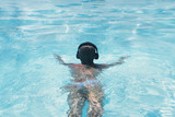 woman in the headphones listening to the  music bathing in a swimming pool