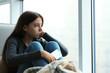 Leinwandbild Motiv Upset teenage girl with smartphone sitting at window indoors. Space for text