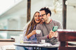 Leinwanddruck Bild - Young cheerful man and woman dating and spending time together in cafe, using phone.