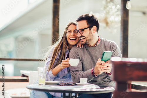 Leinwanddruck Bild Young cheerful man and woman dating and spending time together in cafe, using phone.